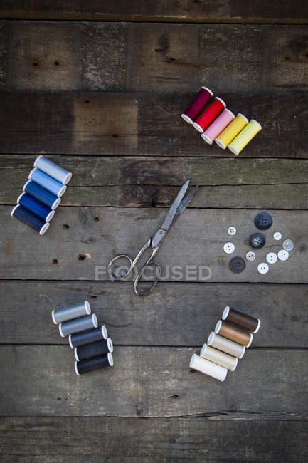 Top view of Scissors, buttons and cotton reels on wood — Stock Photo
