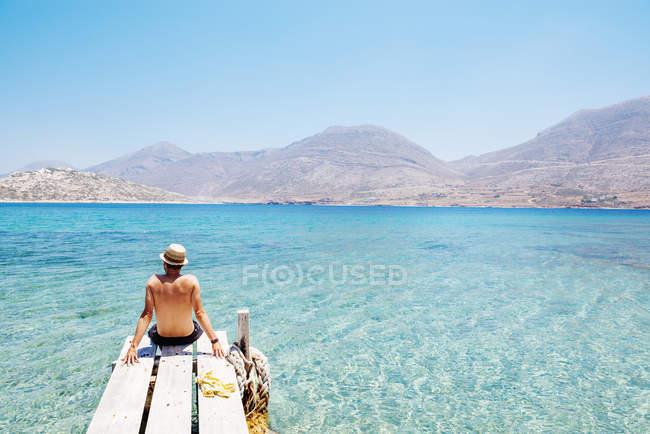 Греція, Крит, острові Amorgos, людина, що сидить на пагорбу дерев'яний причал, Nikouria острів — стокове фото