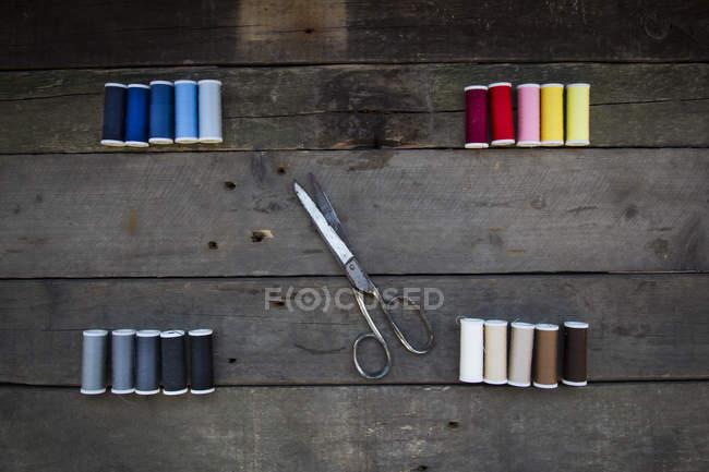 Vue de dessus des ciseaux et des bobines de coton sur bois — Photo de stock
