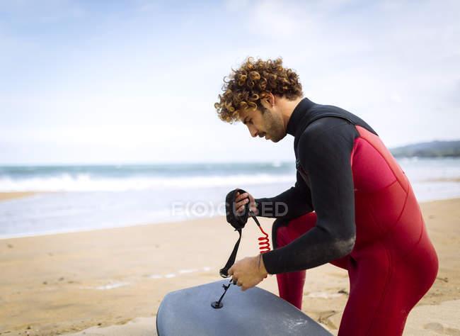 Surfer preparing bodyboard on the beach — Stock Photo