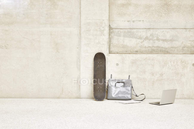Skateboard, bag and laptop at concrete wall — Stock Photo