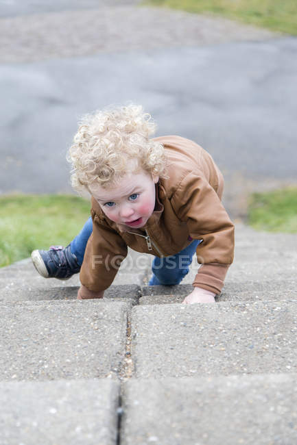 Little girl crawling up stairs — Stock Photo