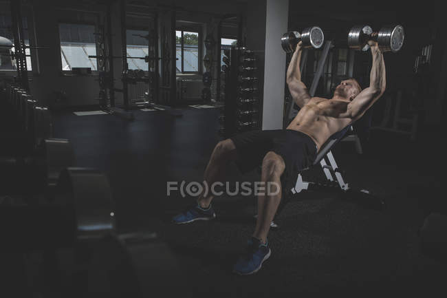 Physical athlete doing bench presses with dumbbells in gym — Stock Photo