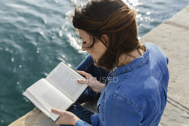 Young woman sitting on dock reading a book — Stock Photo