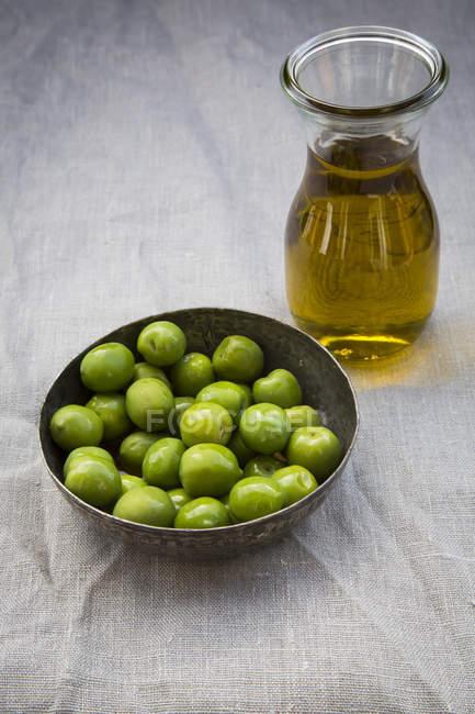 Миска зеленых оливок и графин с оливковым маслом — стоковое фото