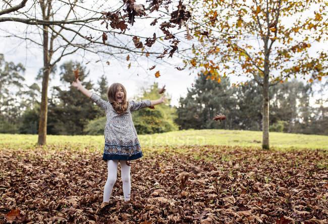 Riendo chica lanzando hojas de otoño en el aire - foto de stock