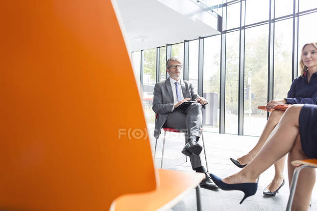 Business people sitting in circle in office and talking — Stock Photo