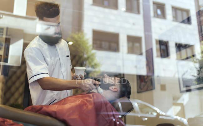 Barber shaving beard of customer behind barber shop window — Stock Photo