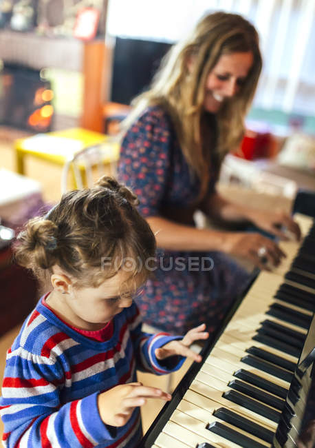Woman and little girl playing piano together — Stock Photo