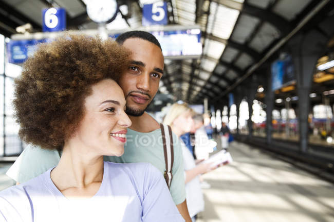 Feliz pareja joven esperando el tren de cercanías - foto de stock