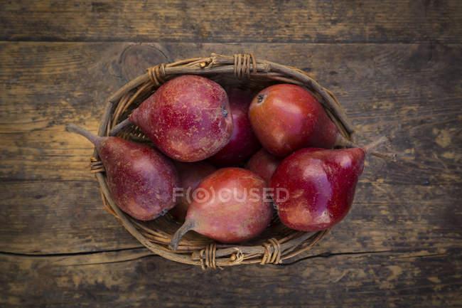 Wickerbasket de orgânicos vermelho Clapp favorito na madeira escura — Fotografia de Stock