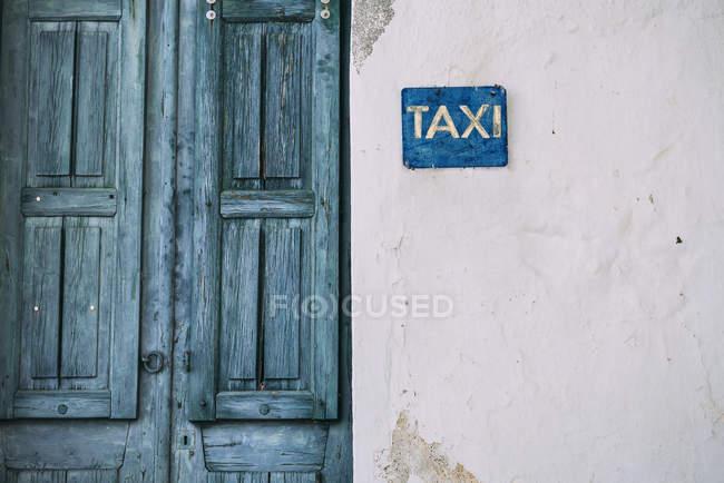 Ciclades, porta de madeira azul e sinal de táxi na fachada — Fotografia de Stock
