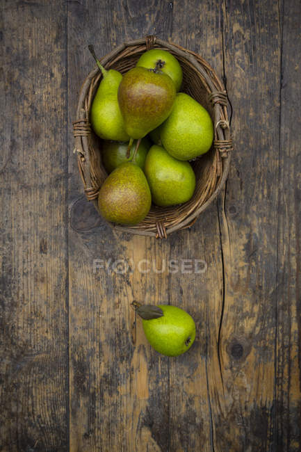 Wicker basket of organic pears on dark wood — Stock Photo