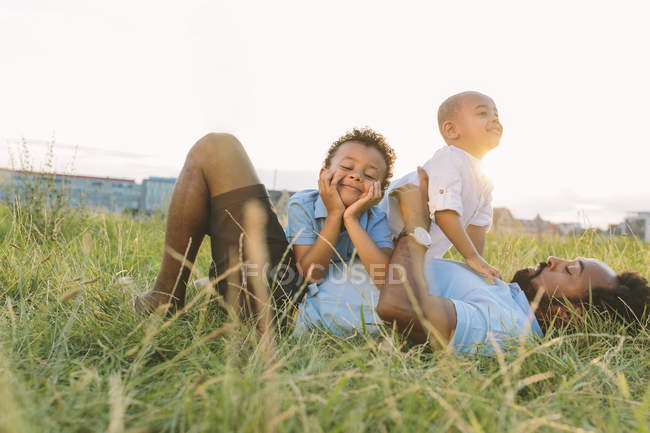 Happy african american father with two sons relaxing in field — Stock Photo