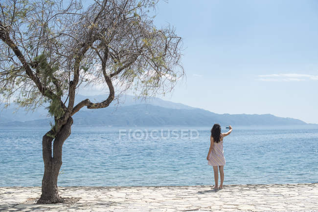 Rear view of woman taking photos with smartphone at coast in Sergoulas, Greece — Stock Photo