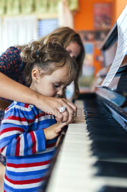 Donna e bambina suonano il pianoforte insieme — Foto stock