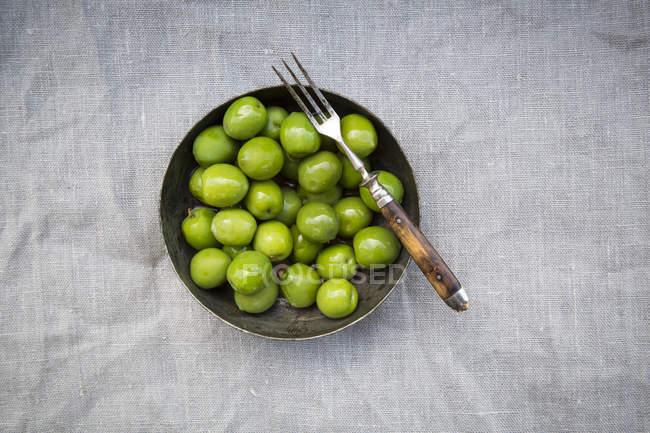 Миска зеленых оливок и вилкой — стоковое фото