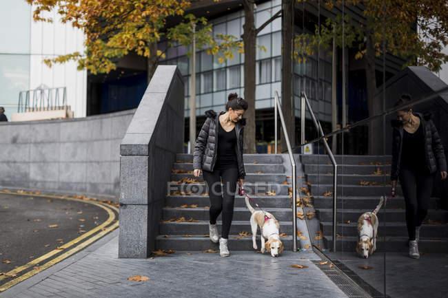 Femme et son chien marchant dans la ville — Photo de stock