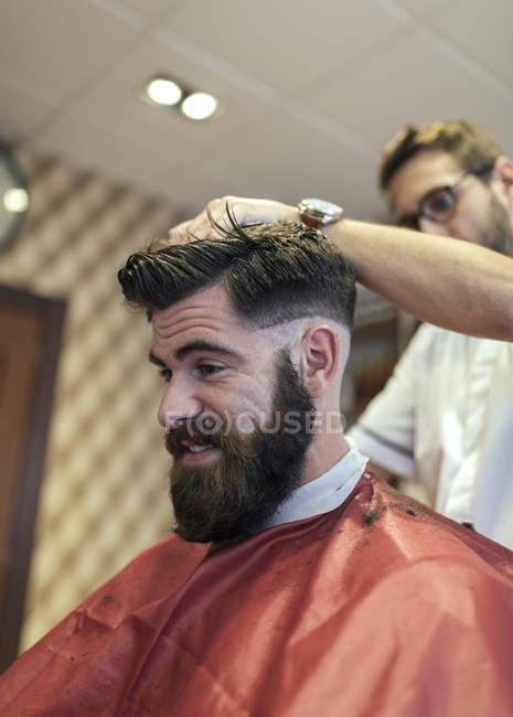 Barber cutting hair of a customer in barbershop — Stock Photo