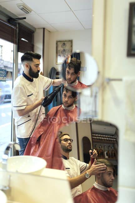 Deux coiffeurs sèche-cheveux et coupe-cheveux de frères jumeaux dans le salon de coiffure — Photo de stock