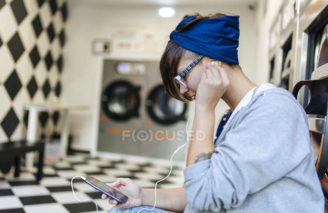 Young woman hearing music with earbuds in a launderette — Stock Photo