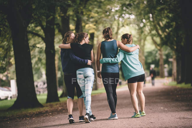 Four female joggers walking in park after fitness training — Stock Photo