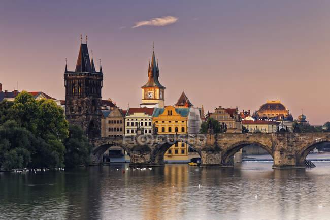 República Checa, Praga, ciudad vieja, río Vlatva, puente de Carlos y el casco antiguo puente de la torre en la noche - foto de stock