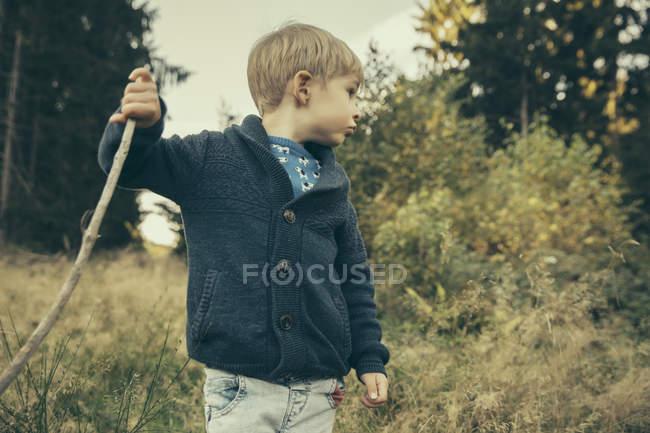 Маленький мальчик исследует лес, ходит по траве с палкой — стоковое фото