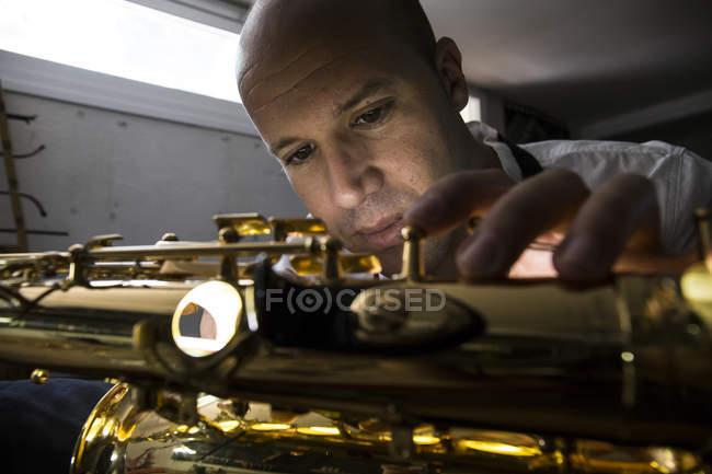Instrument maker dismounting saxophone during repair — Stock Photo