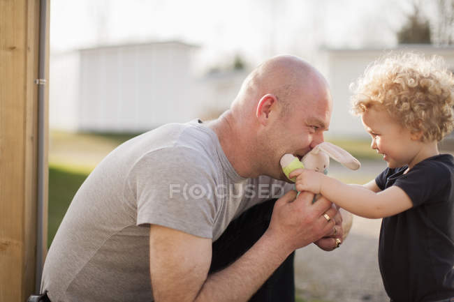 Father and little daughter playing with cuddly toy — Stock Photo