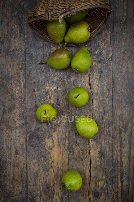 Wicker basket and organic pears on dark wood — Stock Photo