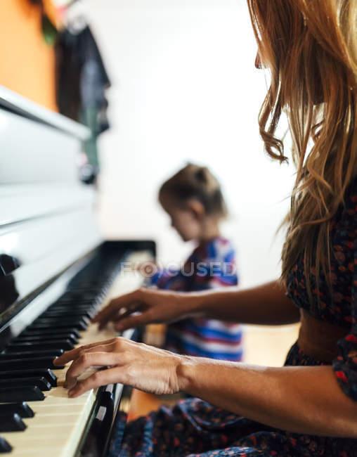 Frau und kleines Mädchen spielen zusammen Klavier — Stockfoto