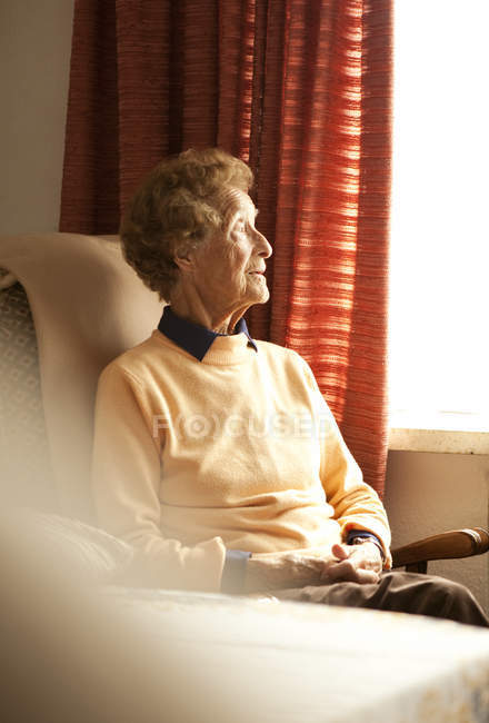 Portrait of aged woman sitting on armchair in her living room looking through the window — Stock Photo
