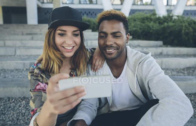 Улыбающаяся молодая пара сидит на ступеньках и смотрит на смартфон — стоковое фото