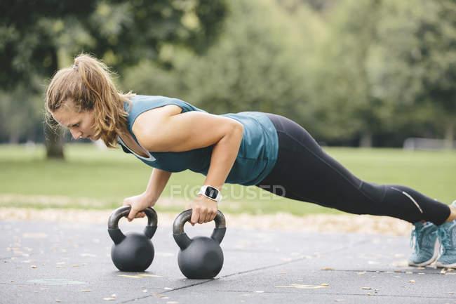 Young woman going pushups on kettlebells — Stock Photo