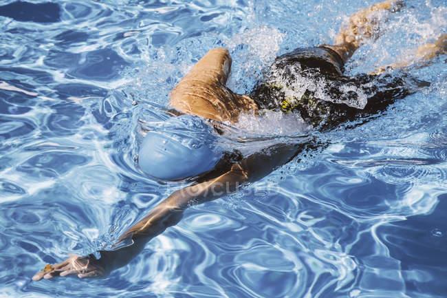 Female triathlete swimming in pool — Stock Photo