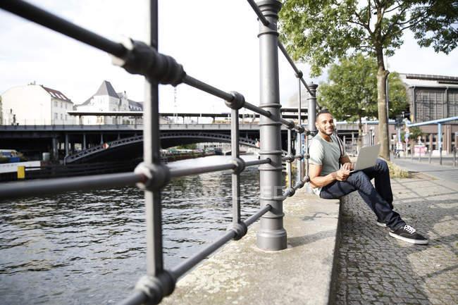 Joven sentado junto al río, usando laptop - foto de stock