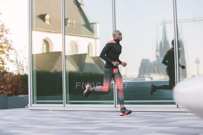 Германия, Кёльн, спортсмен, бегущий у стекла перед зданием с отражением Кёльнского собора — стоковое фото