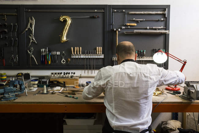 Instrument maker dismounting saxophone during repair — Stock Photo