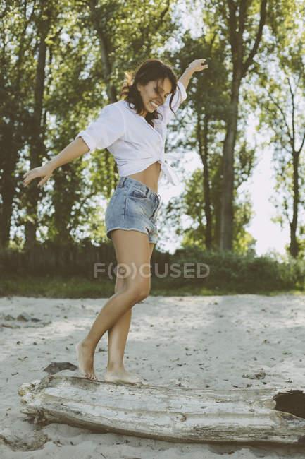 Donna che equilibra il legno morto sulla spiaggia — Foto stock