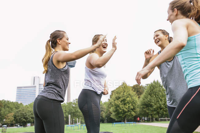 Four happy women high-fiving after outdoor workout — Stock Photo