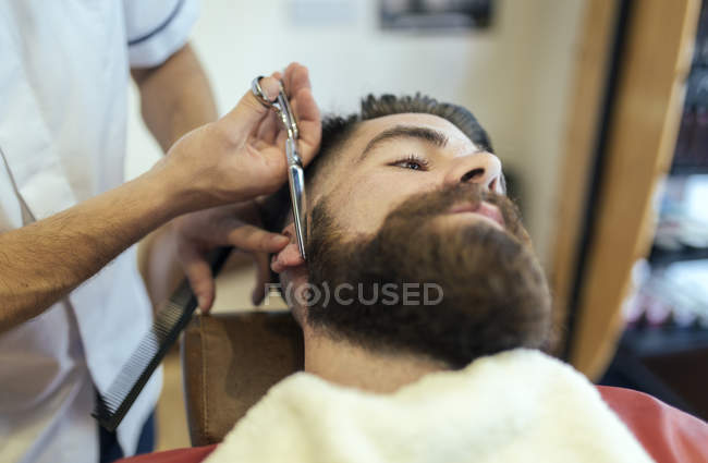 Barber cutting beard of a customer — Stock Photo