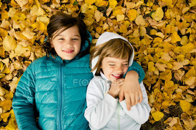 Two girls lying side by side on ground covered with autumn leaves — Stock Photo
