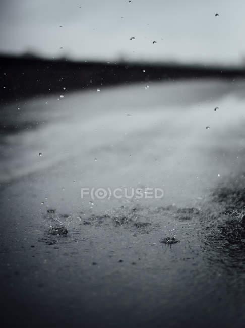 Raindrops splashing on tarmac — Stock Photo