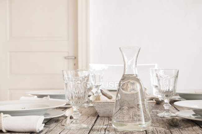 Water carafe and empty glasses on laid table — Stock Photo