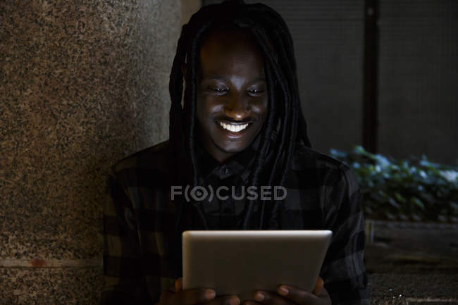 Young black man using digital tablet in the darkness — Stock Photo