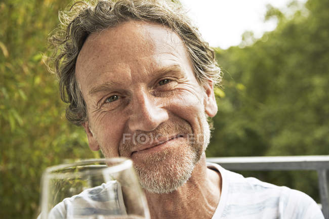Portrait of happy man toasting with glass of wine — Stock Photo