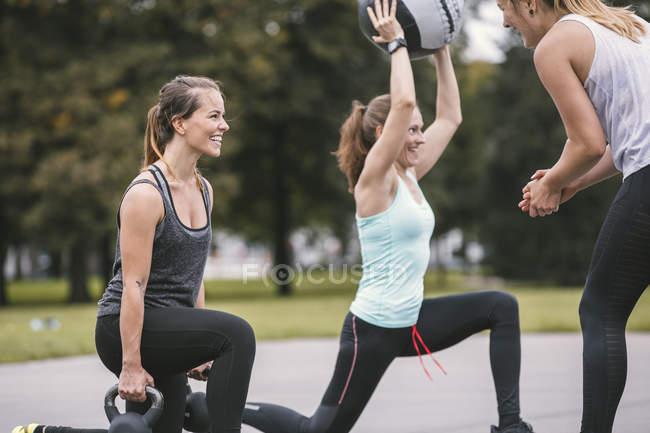 Three women having an outdoor boot camp workout — Stock Photo