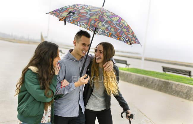 Heureux amis marchant dans la rue avec parapluie — Photo de stock