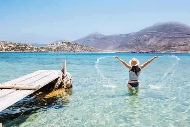 Греція, Кіклади острови, острові Amorgos, жінка плескання в синіх водах на Егейське море поруч із дерев'яними jetty — стокове фото